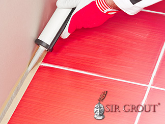 Picture of a Red Tile Floor with White Grout Lines and Caulking